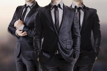 Three men in black suits.